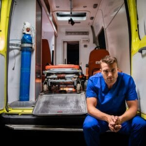 Serious Man In Medical Iniform Sit On The Ambulance Car.
